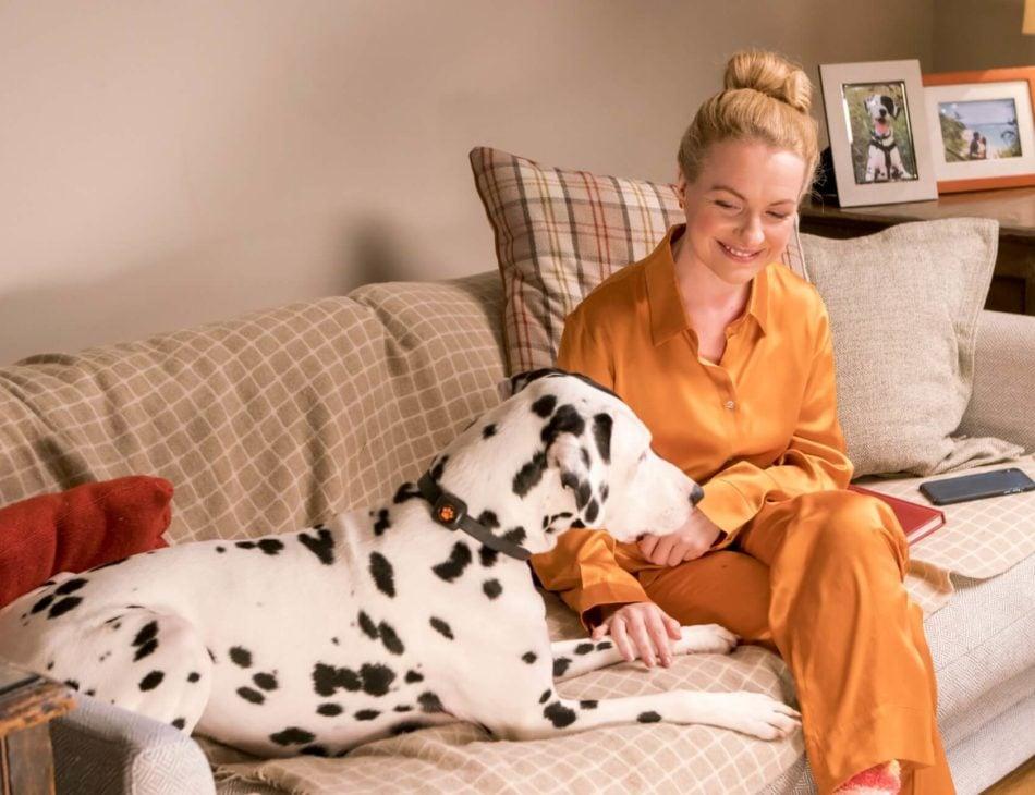 Woman in orange pyjamas sitting on sofa with a dalmatian